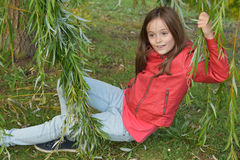 Girl in the leaves of a weeping willow Stock Photography