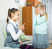 Girl lecturing little sister in domestic interior Stock Photo