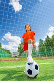 Girl with leg on football in front of woodwork Stock Image