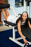 Girl on leg machine. Portrait of smiling girl working out on leg machine in gym Royalty Free Stock Photo