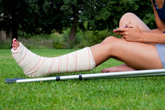 Girl with leg in plaster chatting. Leg in plaster of a girl sitting on the grass writing a text message with her smartphone. Crutches lying down at her side royalty free stock image