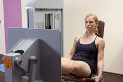 Girl and the leg press Royalty Free Stock Photo