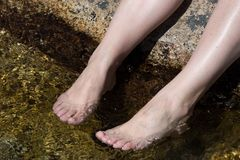 Girl legs. Legs of a girl refreshing in a river royalty free stock photography