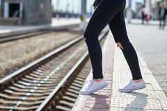 Girl legs on the background of a close-up rail. Legs of a girl in black pants on a background of rails close-up on a sunny day royalty free stock photos