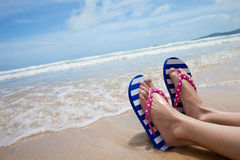 Girl legs in colorful flipflop on beach. Young girl legs in colorful flipflop sandals on sea beach royalty free stock photos