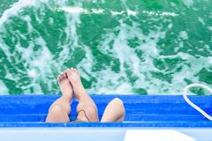 Girl legs hang off edge Passenger boat in ocean.Look at the top. Royalty Free Stock Photography