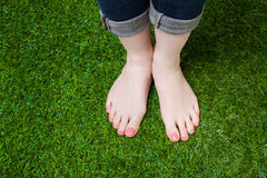 Girl legs in jeans standing  on green grass Royalty Free Stock Photo