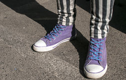 Girl legs with purple sneakers Stock Photography