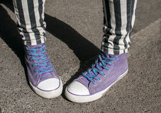 Girl legs with purple sneakers Stock Image