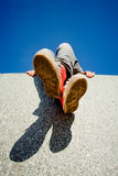 Girl legs in red sneakers. Against blue sky Stock Photo