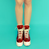 Girl legs in red vintage sneakers Stock Photography