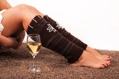Girl legs with warmers and wine glass on carpet floor and white background. Young Girl legs with warmers and wine glass on carpet floor and white background royalty free stock photography