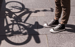 Girl legs wearing black snickers and skinny brown trousers in front of the shadow of a bicycle Royalty Free Stock Images