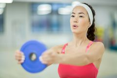 Girl in leisure center. Young woman with heavy disk in stretched arms doing exercise in leisure center Stock Photo
