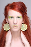 Girl with lemon slices in ears Stock Photography