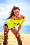 girl in lemon t-shirt laughs shows tongue on beach against sea Stock Images