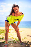 Girl in lemon t-shirt laughs shows tongue on beach against sea Stock Photography