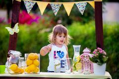 Girl at lemonade stand. Beautiful young girl standing at her lemonade stand in the garden in summer sunny day and sale lemons and lemonade stock photo