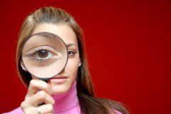 Girl with lens. Nice and beautiful girl holding magnifying lens in front of her eye and making photo interesting for some investigation design Royalty Free Stock Images