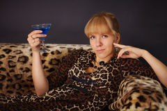 Girl in leopard dress, drinking a blue cocktail Stock Photography