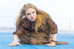 A girl in a leopard dress . Stunning dress on the girl blonde,. Developing from the summer wind. Russia royalty free stock photos
