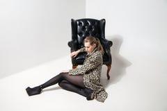 Girl in leopard print coat near armchair Stock Image