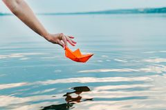 The girl lets down her paper boat to the water with her hand. An orange ship is hanging over the river stock images