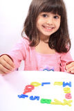 Girl and letters. Young little preschool girl with funny expression playing with letters and numbers Stock Image