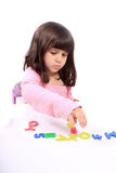 Girl and letters. Young little preschool girl with funny expression playing with letters and numbers Stock Photography
