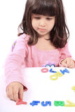 Girl and letters and numbers. Young little preschool girl with funny expression playing with letters and numbers Royalty Free Stock Images