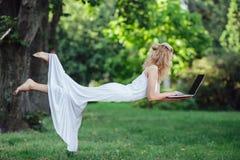 Girl levitates with laptop Stock Photo