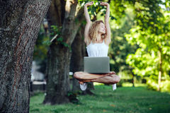 Girl levitates with laptop Stock Photography