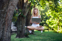 Girl levitates with laptop Royalty Free Stock Photo