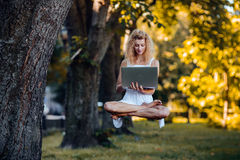 Girl levitates with laptop Royalty Free Stock Photography