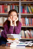 Girl in library. Portrait of clever student looking at camera and smiling in college library royalty free stock photos