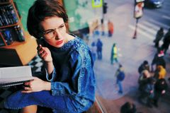 Girl in the library or the bookstore looking out the window with. A book in his hand. It is thoughtful and glasses. On the street people can see Royalty Free Stock Images