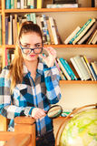 Girl in library with globe and magnifying glass Royalty Free Stock Photos
