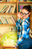 Girl in library pointing to globe Stock Photo