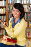 Girl at library reading a e-book Stock Images