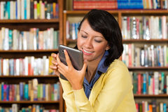 Girl at library reading a e-book Royalty Free Stock Image
