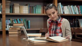 Girl at Library Table. Smiling caucasian girl studying in library, doing research with pleasure with use of the internet and books, wearing checked casual shirt stock video footage