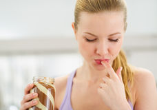 Girl licking chocolate cream from finger Stock Images