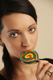 Girl licking a coloful lollipop. Royalty Free Stock Photos