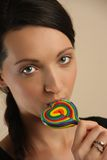 Girl licking a coloful lollipop. Stock Photo
