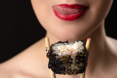 Girl licking lips with roll Stock Photography