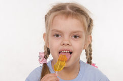 Girl licking a lollipop Royalty Free Stock Image