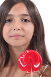 Girl licking a lollipop Stock Image