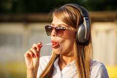 Girl licking a lollipop. Music headphones Royalty Free Stock Photos