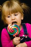 Girl licking lollipop Stock Image