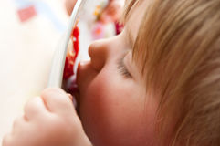 Girl licking plate clean. Side portrait of cute young preschool girl or toddler licking sauce off plate after meal royalty free stock images